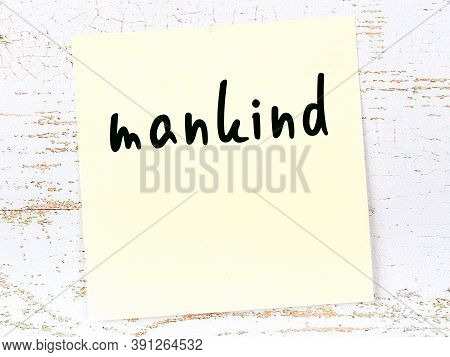 Yellow Sticky Note On Wooden Wall With Handwritten Inscription Mankind