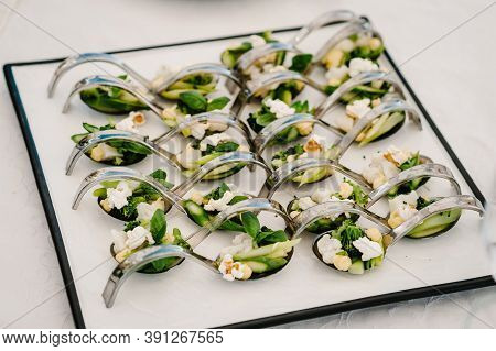 Gourmet Appetizers On Metal Spoons, Variety Of Mini Appetizer With Different Toppings On Plate. Fron
