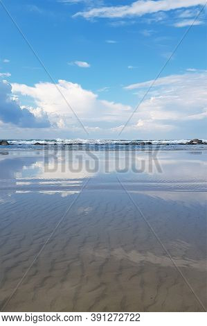 Blue Sky And Clouds Are Reflected In The Water. Sea Shore. The Concept Of Calm And Conciliation. Ver