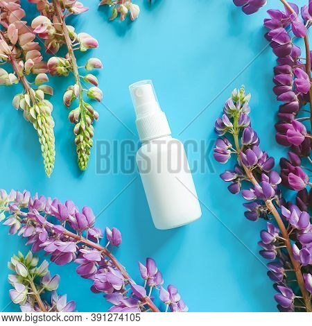 Top View And Close-up Of White Plastic Spray Bottle Mock-up And Flower Lupine Composition On A Blue