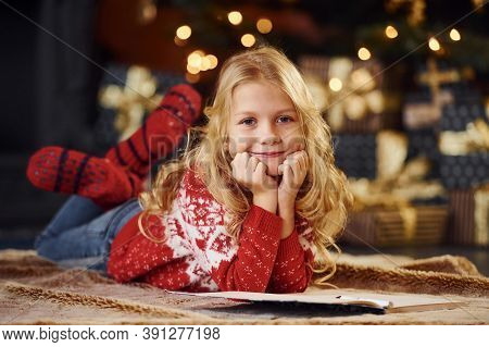 Cute Little Girl In Red Festive Sweater Indoors Lying Down Celebrating New Year And Christmas Holida