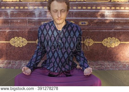 Buddhist Man In A Purple Shirt Meditates On The Background Of A Buddhist Statue