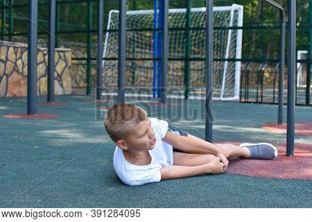 Boy Kid Banged On Gym Outside, Child Injured Limb On Playground, Sports Injury Of Boy's Leg. Young A