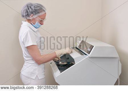 Female Nurse Doing Sterilization Of Dental Medical Instruments In Autoclave