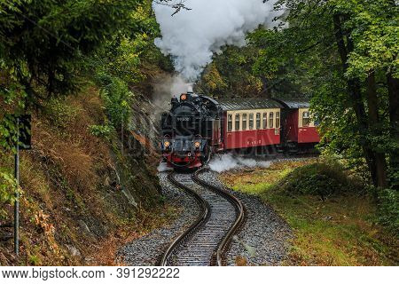 Steam Locomotive With Wagon In A Valley In The Harz Mountains. Narrow Gauge Railway In The Mountains