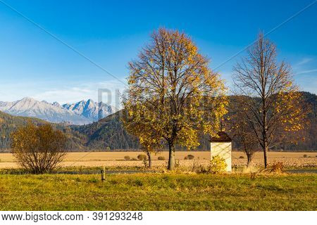 chapel with a tree in Low Tatras with background High Tatras, Slovakia
