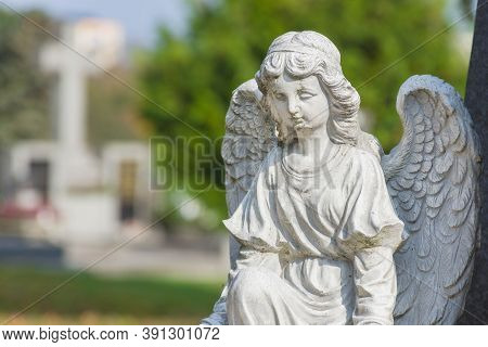 Sculpture Of A Little Angel On A Tomb In Cemetery. Selective Focus