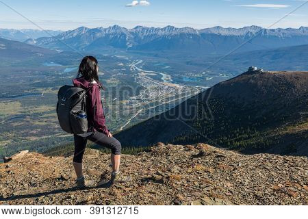 Woman Hiking And Standing In Jasper National Park With The Jasper Skytram In The Distance.