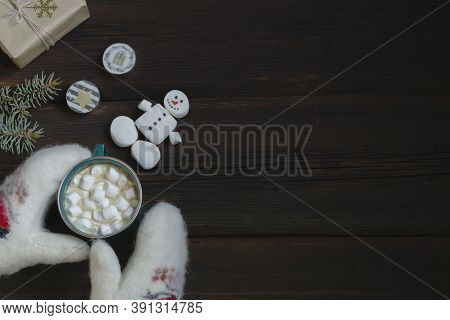 Female Hands In White Woolen Mittens Hold A Cup Of Hot Drink With Marshmallows. New Year's Gift, Can