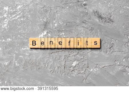 Benefits Word Written On Wood Block. Benefits Text On Cement Table For Your Desing, Top View Concept