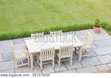 Wooden Garden Furniture On A Patio Terrace In A Uk Back Garden With Lawn