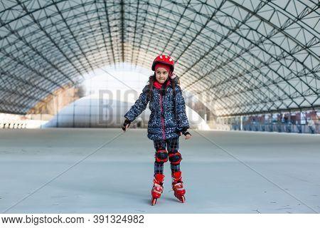 Little Cute Happy Girl Rollerblading In A Big Hangar