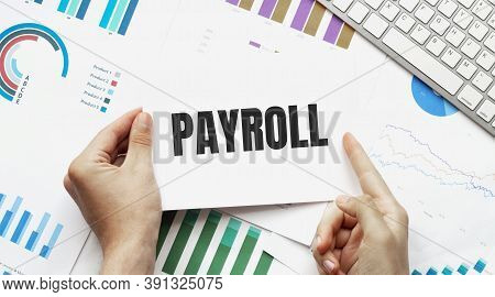 Businessman Holding A Card With Text Payroll. Keyboard, Diagram And White Background