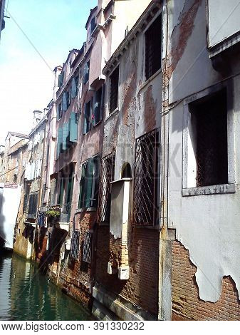 Venice, Italy, May 30, 2020. Narrow Canal In Venice. Leaking Plaster From The Building Due To High H