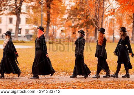 Going To A Halloween Party. Five Women As Witches Go To The Sabbath, A Group Of Witches Or Goths In