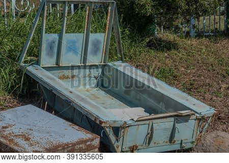 Old Blue Flatbed Trailer Parked In Grassy Area On The Side Of A Mountain.