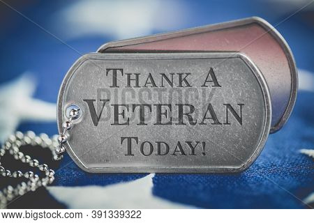 Worn US American dog tags on USA flag with Thank a Veteran Today engraved text
