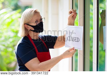 Owner Hanging Closed Sign Board On Shop Entrance.
