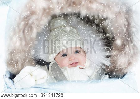Baby In Stroller In Winter Snow. Kid In Pram. Child Wearing Warm Jacket And Knitted Hat Wrapped In F