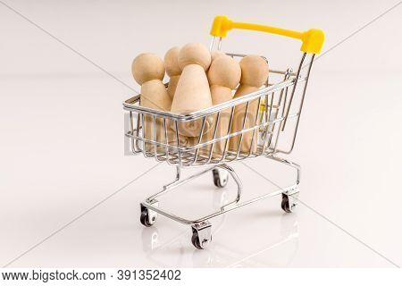 Wooden Stick Figure In A Trolley On A White Background. Human Trafficking Or Human Resource For Work