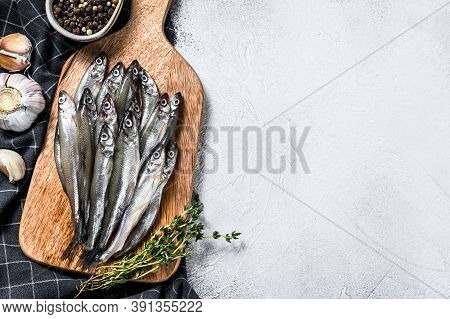 Fresh Raw Sea Small Fish Smelt. Gray Background. Top View. Copy Space