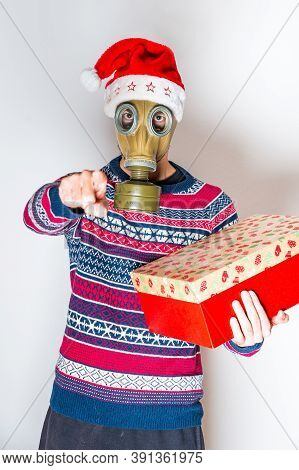 Hey You! Person In Gas Mask With The Gift In The Hand And Christmas Hat