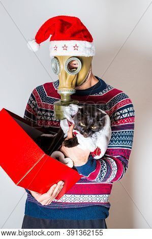 Man In Gas Mask Taking Of The Cat Out Of The Christmas Gift With Christmas Hat On Light Background