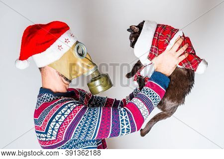 Person In Gas Mask And Christmas Hat Watching At His Christmas Black Cat