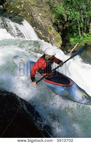Woman Canoeing Down Fast Flowing Water