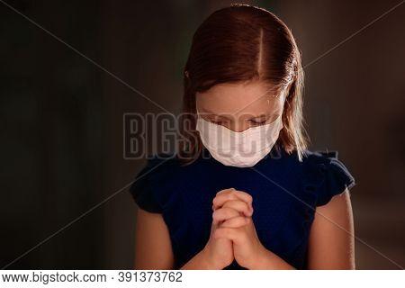 Pray For Xxx. Child In Face Mask Praying. Little Girl In Hospital Chapel Or Church During Coronaviru