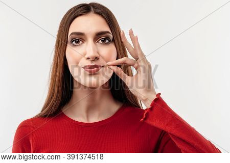 Young Woman With Long Chestnut Hair In Casual Red Sweater, Showing Zip Gesture As If Shutting Mouth