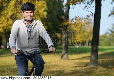 Smiling mature Caucasian man in casual clothing and bike helmet rides on his city bicycle in an autumn city park and looking at camera