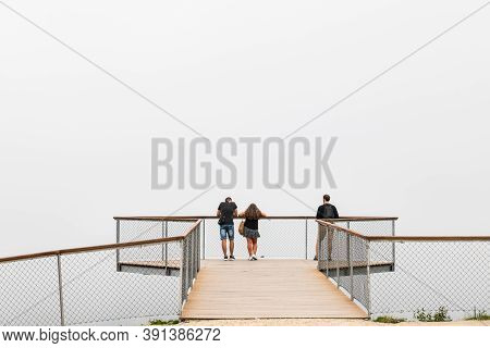 Pontevedra, Spain - August 25, 2020: A Small Group Of People Wait For The Fog To Rise On A Modern Lo