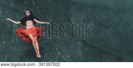 Aerial view of a beautiful woman dancing  in the sea