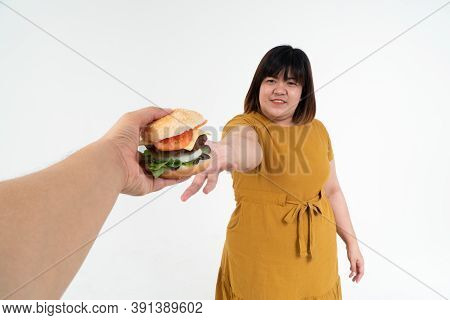Hungry Overweight Young Asian Woman Holding Hamburger On Isolated Background, Her Hungry All Time An