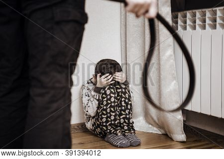Aggressive Parent With Belt And Frightened Child In Corner. Domestic Violence. Abused Child, Aggress