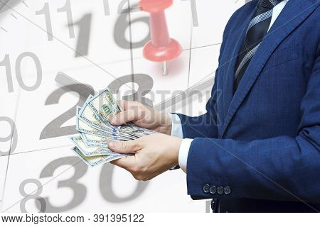 Businessman With Money In Hand Against The Background Of A Calendar With A Date Stamp Pin And Arrows