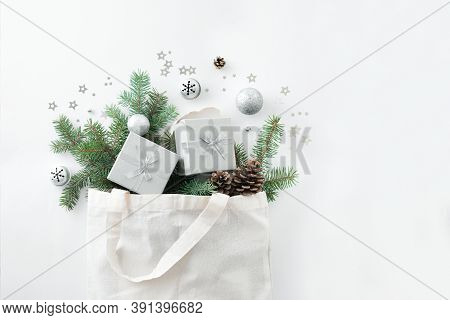 Christmas Composition. Eco Bag With Christmas Decor, Gift Boxes, Pine Branches On White Background.