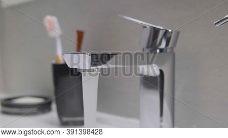 Water Runs From The Tap Into The Sink. Modern Water Tap In The Bathroom With Running Flowing Water I