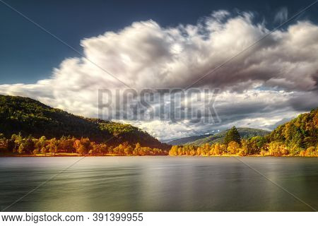 Autumn Colors On Lake Ghirla In Valganna With Clouds Moved By The Wind, Long Time Exposure