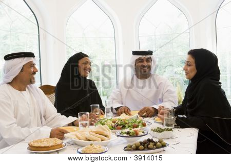 Two couples sitting at dinner table smiling (high key) poster