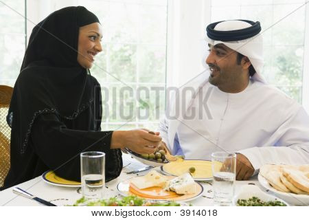 Couple sitting at dinner table smiling (high key) poster