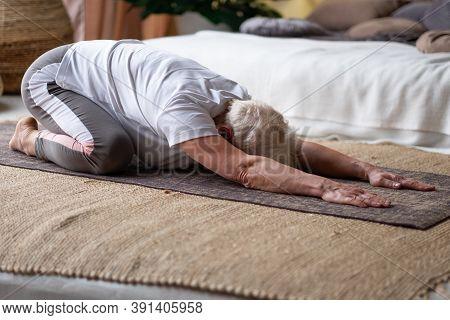 Senior Woman Practicing Yoga At Home Doing Balasana Position