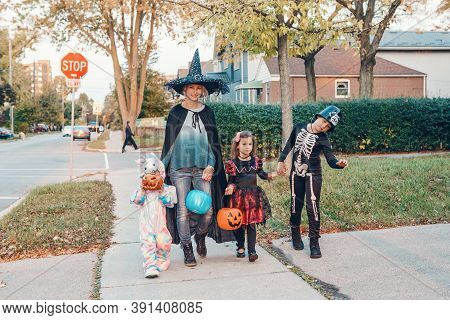 Trick Or Treat. Mother With Children Going To Trick Or Treat On Halloween Holiday. Mom With Kids In