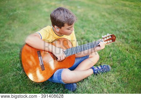Hard Of Hearing Preteen Boy Playing Guitar Outdoor. Child With Hearing Aids In Ears Playing Music An
