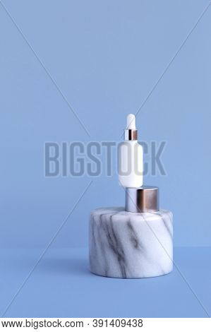Natural Organic Cosmetic Serum In A White Glass Bottle With A Dropper On A Marble Aluminum Pedestal