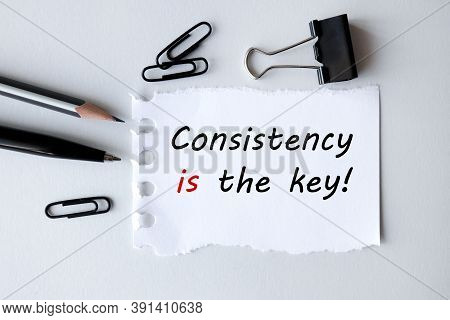 Consistency Is The Key, Text On White Paper On Gray Background