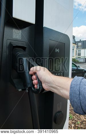 Hand Holding Gas Pump In Gas Tank. Fuel, Oil, Gas Filling - Close Up Gas Or Electric Station.