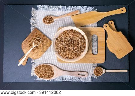 Buckwheat, A Bunch Of Buckwheat Groats Next To A Village Spoon With Buckwheat In It, On A Black Back