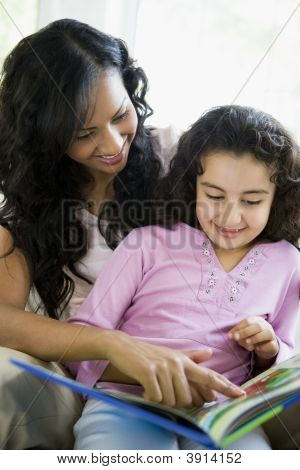 Middle Eastern Mother And Child Reading At Home Together
